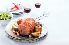 El cerdo de carne asada con la manzana en una tabla fijó para la celebración Imágenes de archivo libres de regalías