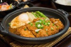 El cerdo de la chuleta hirvió a fuego lento en salsa del miso con el huevo frito en la placa caliente Fotografía de archivo