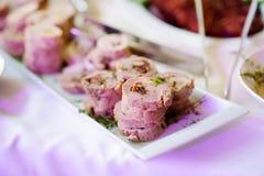 El cerdo delicioso rueda con las verduras servidas en un partido o una recepción nupcial Fotografía de archivo