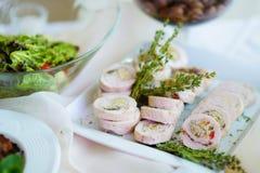El cerdo delicioso rueda con las verduras servidas en un partido o una recepción nupcial Imagenes de archivo