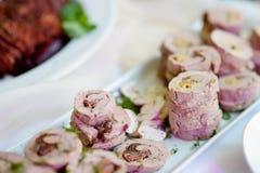 El cerdo delicioso rueda con las verduras servidas en un partido o una recepción nupcial Fotos de archivo