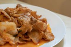El cerdo rayado cortado frito está en el plato Foto de archivo