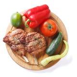 El cerdo y las verduras asados a la parrilla en una tabla de cortar aislaron la visión superior Foto de archivo