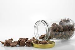 El cereal del chocolate se derrama hacia fuera de la botella de cristal, en el backgroun blanco Imagenes de archivo
