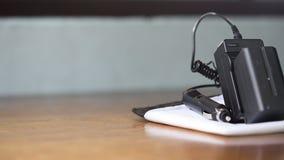 El chager de la batería pone en la hoja blanca, en la tabla de madera Fotografía de archivo libre de regalías