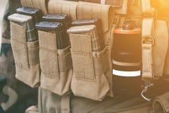 El chaleco del ejército con los cuellos cargados un Walkietalkie aturde los palillos luminosos de las granadas que se colocan en  Fotos de archivo