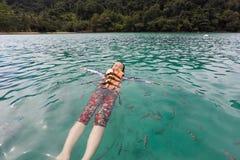 El chaleco salvavidas asiático feliz del desgaste de la muchacha, goza el jugar en el grupo del mar, del turista y de los pescado fotografía de archivo libre de regalías