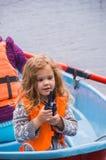 El chaleco salvavidas de la muchacha, niño en un barco, dice en la radio Foto de archivo libre de regalías