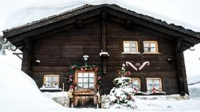El chalet cubierto con nieve y adornado para la Navidad, enfoca adentro metrajes