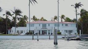 El chalet moderno en los colores blancos entre la naturaleza tropical en la orilla del ` s de la bahía con el embarcadero privado almacen de metraje de vídeo