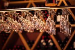 El champán de los vidrios cuelga sobre el contador de la barra en la barra Fotografía de archivo libre de regalías