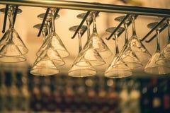 El champán de los vidrios cuelga sobre el contador de la barra en la barra Foto de archivo libre de regalías