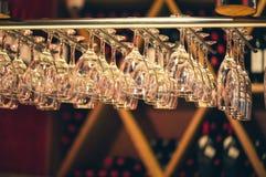 El champán de los vidrios cuelga sobre el contador de la barra en la barra Fotos de archivo libres de regalías