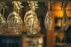 El champán de los vidrios cuelga sobre el contador de la barra en la barra Imágenes de archivo libres de regalías