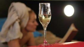 El champán del primer fluye en un vidrio La mujer hermosa miente en una cama y lee un libro Cámara lenta almacen de video