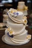 El champán de tres gradas coloreó el pastel de bodas con las flores amarillas y púrpuras Imagenes de archivo
