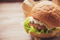 El cheeseburger delicioso apiló alto con una empanada de carne de vaca jugosa, un queso, una lechuga fresca, una cebolla y un tom foto de archivo libre de regalías