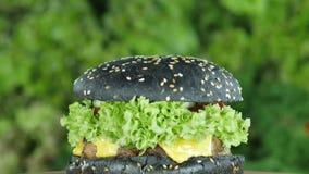 El cheeseburger o la hamburguesa con carne de vaca y pepinos y un bollo negro gira en un círculo en un fondo borroso almacen de video