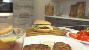 El cheeseburger recientemente cocinado miente en el tablero de la cocina en la cocina, al lado de los ingredientes para los alime almacen de video