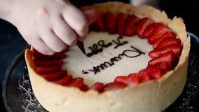 El chef de repostería adorna un pastel de queso con la inscripción de las fresas con un bolso de cocinar y una crema marrón metrajes