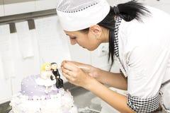 El chef de repostería adorna una torta Imagen de archivo libre de regalías