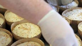 El chef de repostería da la aspersión del polvo del azúcar en la pasta para el pan del dulce de pascua almacen de video