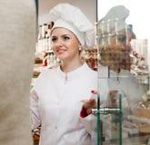 El chef de repostería de la mujer joven saluda a visitantes en la puerta Imagenes de archivo