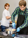 El chef de repostería elabora cerveza la pasta Ella le ayuda a cocinar en la cocina Fotos de archivo
