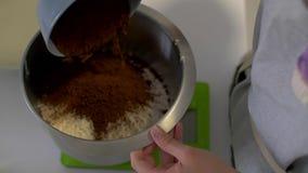 El chef de repostería vierte el cacao en un cuenco de harina metrajes