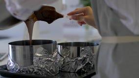 El chef de repostería vierte el chocolate caliente en una cacerola metrajes