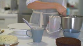 El chef de repostería vierte la crema en un plato de la hornada metrajes