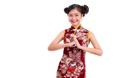 El cheongsam que lleva y la bendición de la mujer asiática joven de la belleza o saludan Fotografía de archivo