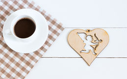 El chocolate caliente con la servilleta y el cupido figuran en un fondo blanco Imagenes de archivo