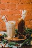El chocolate caliente tradicional dos con las melcochas y el caramelo se pega sobre la toalla blanca del enchufe, fondo oscuro de Imagen de archivo