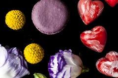 El chocolate del corazón florece y los macarrones en negro desde arriba Foto de archivo