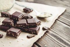 El chocolate junta las piezas con sésamo en una tabla rústica Foto de archivo