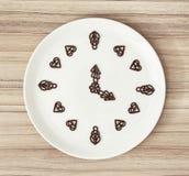 El chocolate oscuro adorna en la forma del reloj Imagen de archivo