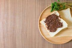 El chocolate se separó en la rebanada de pan en la placa de madera Fotografía de archivo libre de regalías