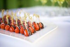 El chocolate sumergió las fresas en una placa en una tabla de la boda Fotografía de archivo