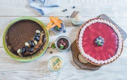 El chocolate y la baya se apelmazan con los postres en un vidrio de queso y de bayas en una tabla de madera Imagen de archivo