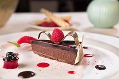 El chocolate y la paleta de las frambuesas, sirvieron en una placa blanca fotografía de archivo libre de regalías