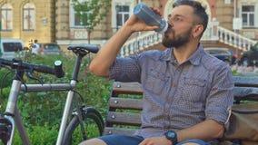 El ciclista bebe el agua en el banco almacen de video