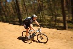 El ciclista compite en la raza de la élite MTB en el bosque Imagenes de archivo