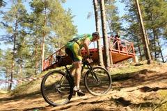 El ciclista compite en la raza de la élite MTB en el bosque Imagen de archivo