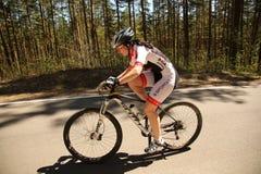 El ciclista compite en la raza de la élite MTB en el bosque Imagen de archivo libre de regalías