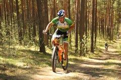 El ciclista compite en la raza de la élite MTB en el bosque Foto de archivo libre de regalías