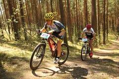El ciclista compite en la raza de la élite MTB en el bosque Fotos de archivo libres de regalías