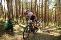 El ciclista compite en la raza de la élite MTB en el bosque Imágenes de archivo libres de regalías