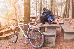 El ciclista con la bici y el teléfono móvil de montaña descansa en una área de picnic en una mañana fría del invierno fotografía de archivo