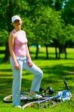 El ciclista de la mujer permanece cerca de la bici de mentira Fotografía de archivo
